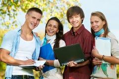 Gruppo di giovani allievi sorridenti all'aperto Fotografie Stock Libere da Diritti