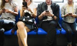 Gruppo di giovani amici adulti che utilizzano gli smartphones nel sottopassaggio Fotografia Stock