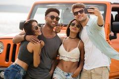 Gruppo di giovani amici allegri che parlano insieme un selfie Fotografie Stock
