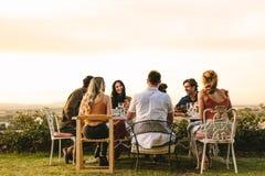 Gruppo di giovani amici cenando partito fotografia stock