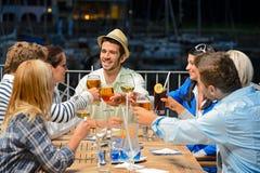 Giovani amici che clinking il ristorante di notte di vetro Fotografia Stock