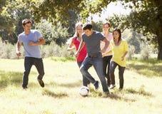 Gruppo di giovani amici che giocano a calcio nella campagna fotografie stock