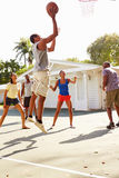 Gruppo di giovani amici che giocano la partita di pallacanestro Fotografia Stock