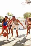 Gruppo di giovani amici che giocano la partita di pallacanestro Fotografie Stock