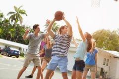 Gruppo di giovani amici che giocano la partita di pallacanestro Fotografia Stock Libera da Diritti