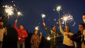 Gruppo di giovani amici che hanno un partito della spiaggia Amici che ballano e che celebrano con le stelle filante nel tramonto  video d archivio