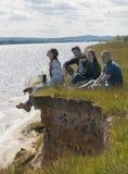 Gruppo di giovani amici che si siedono sul sull'orlo di una collina che gode della ricreazione all'aperto fotografie stock libere da diritti