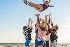 Gruppo di giovani amici dei pantaloni a vita bassa che corrono insieme lungo la spiaggia Fotografia Stock