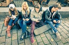 Gruppo di giovani amici dei pantaloni a vita bassa che giocano con lo smartphone