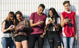 Gruppo di giovani amici dell'adolescente che raffreddano insieme fuori facendo uso del concetto sociale di media dello smartphone Fotografie Stock