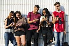 Gruppo di giovani amici dell'adolescente che raffreddano insieme fuori facendo uso del concetto sociale di media dello smartphone Fotografia Stock Libera da Diritti
