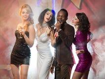 Gruppo di giovani amici felici divertendosi, vacationing e cantando karaoke Immagine Stock