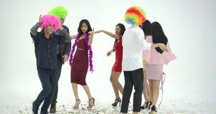 Gruppo di giovani asiatici divertendosi ballare come pazzo al fondo bianco La gente con il partito, celebrazione, godimento archivi video