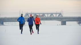 Gruppo di giovani atleti che corrono tecnicamente nella foresta di inverno archivi video