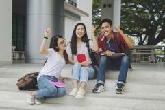 Gruppo di giovani attraenti che per mezzo di un computer portatile e di una compressa, sitt Fotografia Stock Libera da Diritti