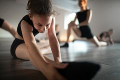 Gruppo di giovani ballerini adatti che praticano durante la scuola della classe immagine stock libera da diritti