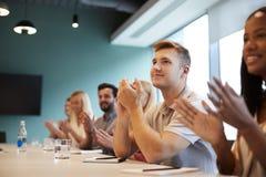 Gruppo di giovani candidati che si siedono alla presentazione d'applauso della Tabella della sala del consiglio al giorno laureat immagine stock libera da diritti