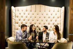 Gruppo di giovani che celebrano e che tostano con il vino bianco Fotografia Stock