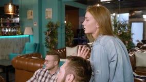 Gruppo di giovani che chiacchierano in un caffè stock footage