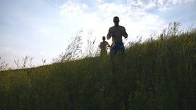 Gruppo di giovani che corrono giù la collina verde sopra cielo blu con il chiarore del sole al fondo Gli atleti maschii sta pareg Fotografia Stock