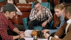 Gruppo di giovani che discutono un nuovo progetto in un caffè video d archivio