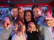 Gruppo di giovani che hanno divertimento in barra occupata Immagini Stock