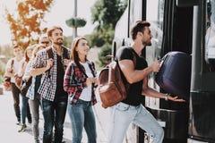 Gruppo di giovani che imbarcano sul bus di viaggio fotografie stock libere da diritti