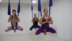 Gruppo di giovani che praticano yoga aerea in studio bianco con le amache Movimento lento stock footage