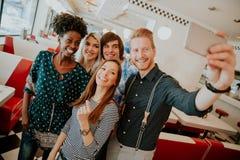 Gruppo di giovani che prendono selfie con il telefono cellulare fotografia stock