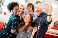 Gruppo di giovani che prendono selfie con il telefono cellulare immagini stock