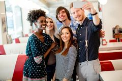 Gruppo di giovani che prendono selfie con il telefono cellulare fotografia stock libera da diritti