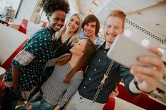 Gruppo di giovani che prendono selfie con il telefono cellulare fotografie stock libere da diritti