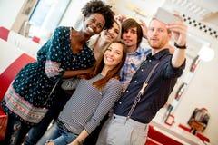 Gruppo di giovani che prendono selfie con il telefono cellulare immagine stock libera da diritti