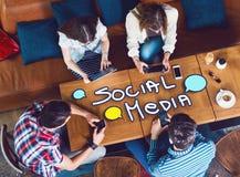 Gruppo di giovani che si siedono ad un caffè, con i cellulari e le compresse immagini stock libere da diritti