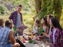 Gruppo di giovani che si siedono intorno ad una tavola fuori Godono di di chiacchierare e bere le birre fotografia stock