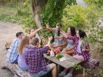 Gruppo di giovani che si siedono intorno ad una tavola fuori Godono di di chiacchierare e bere le birre fotografia stock libera da diritti