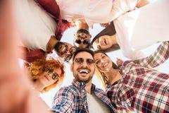 Gruppo di giovani che stanno in un cerchio, facente un selfie immagini stock libere da diritti