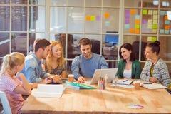 Gruppo di giovani colleghi che per mezzo del computer portatile Fotografie Stock