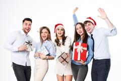 Gruppo di giovani con i regali divertendosi su un fondo bianco Fotografie Stock