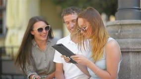 Gruppo di giovani con le note, le penne e la compressa spendere tempo fuori All'aperto un ritratto di tre studenti che parlano e archivi video