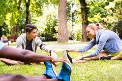 Gruppo di giovani corridori che allungano e che si scaldano nel parco Fotografie Stock Libere da Diritti