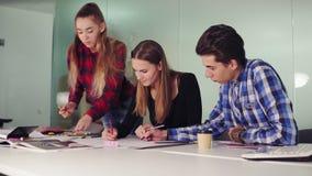 Gruppo di giovani dei pantaloni a vita bassa che lavorano insieme nell'ufficio moderno Giovani professionisti che fanno gli schiz stock footage