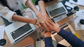 Gruppo di giovani della corsa mista che fanno le mani in pila in ufficio Vista da tavolino della Tabella di legno da sopra 4K stock footage