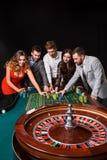 Gruppo di giovani dietro la tavola delle roulette su fondo nero Fotografia Stock Libera da Diritti