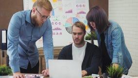 Gruppo di giovani direttori aziendali che analizzano i dati facendo uso del computer nell'ufficio stock footage