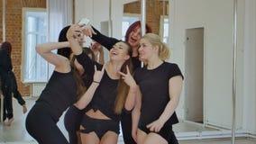Gruppo di giovani donne che prendono un selfie durante la classe di ballo del palo video d archivio