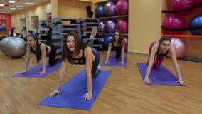 Gruppo di giovani donne nella classe di forma fisica che fa gli esercizi per le gambe stock footage