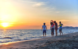 Gruppo di giovani felici che ballano alla spiaggia sul bello tramonto di estate Fotografia Stock Libera da Diritti