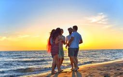 Gruppo di giovani felici che ballano alla spiaggia sul bello tramonto di estate Immagine Stock