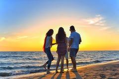 Gruppo di giovani felici che ballano alla spiaggia sul bello tramonto di estate Immagini Stock